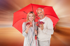 Composite image of smiling couple showing autumn leaves under umbrella. Smiling couple showing autumn leaves under umbrella against sunrise over field with tree Royalty Free Stock Photography