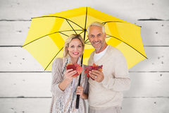 Composite image of smiling couple showing autumn leaves under umbrella Stock Photos