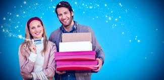 Composite image of smiling couple showing credit card and carrying boxes Royalty Free Stock Image