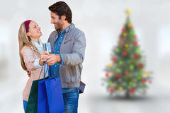 Composite image of smiling couple showing credit card and shopping bags Royalty Free Stock Photo