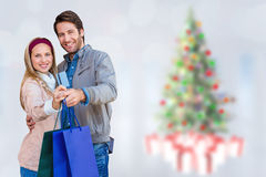 Composite image of smiling couple showing credit card and shopping bags. Smiling couple showing credit card and shopping bags against blurry christmas tree in Royalty Free Stock Photo