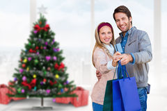 Composite image of smiling couple showing credit card and shopping bags Stock Images