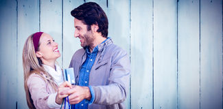 Composite image of smiling couple showing credit card and shopping bags Royalty Free Stock Photos