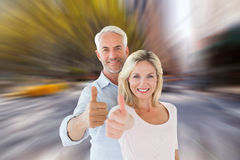 Composite image of smiling couple showing thumbs up together Royalty Free Stock Images