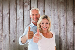 Composite image of smiling couple showing thumbs up together Royalty Free Stock Photo