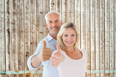 Composite image of smiling couple showing thumbs up together Stock Photos