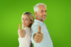 Composite image of smiling couple showing thumbs up together Royalty Free Stock Photography