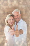 Composite image of smiling couple showing thumbs up together Royalty Free Stock Image