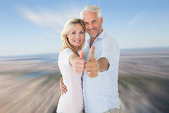 Composite image of smiling couple showing thumbs up together Stock Images