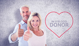 Composite image of smiling couple showing thumbs up together Stock Photo