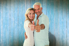 Composite image of smiling couple showing thumbs up together Royalty Free Stock Photos