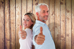 Composite image of smiling couple showing thumbs up together Stock Image