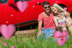 Composite image of smiling couple sitting on the grass having picnic together Royalty Free Stock Photo