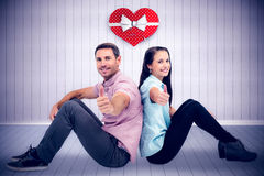 Composite image of  smiling couple sitting showing thumbs up Stock Images