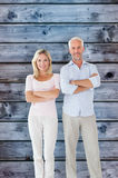 Composite image of smiling couple standing with arms crossed stock image