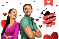 Composite image of smiling couple standing back to back with arms crossed Stock Photos