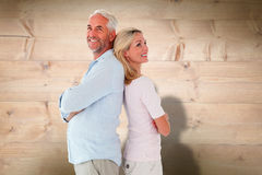 Composite image of smiling couple standing leaning backs together Stock Photo