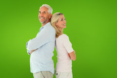 Composite image of smiling couple standing leaning backs together. Smiling couple standing leaning backs together against green vignette royalty free stock photos