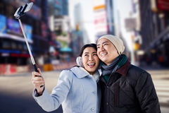 Composite image of smiling couple taking selfie Royalty Free Stock Photography