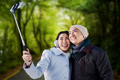 Composite image of smiling couple taking selfie. Smiling couple taking selfie against country road Stock Images