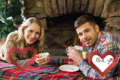 Composite image of smiling couple with tea cups in front of lit fireplace Stock Images
