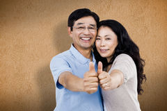 Composite image of smiling couple with thumbs up Royalty Free Stock Images