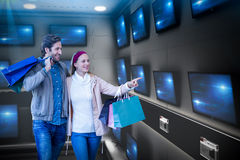 Composite image of smiling couple walking hand in hand and going window shopping. Smiling couple walking hand in hand and going window shopping against Stock Images