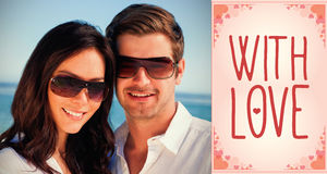 Composite image of smiling couple wearing sunglasses and looking at camera Stock Image
