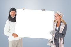 Composite image of smiling couple in winter fashion holding poster Royalty Free Stock Photo