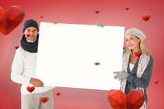 Composite image of smiling couple in winter fashion holding poster Stock Images