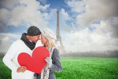 Composite image of smiling couple in winter fashion posing with heart shape Stock Image