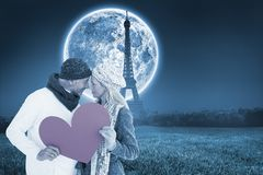 Composite image of smiling couple in winter fashion posing with heart shape Royalty Free Stock Images