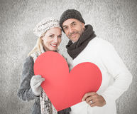 Composite image of smiling couple in winter fashion posing with heart shape Stock Photos
