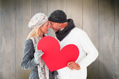 Composite image of smiling couple in winter fashion posing with heart shape. Smiling couple in winter fashion posing with heart shape against wooden planks Royalty Free Stock Photography