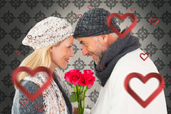 Composite image of smiling couple in winter fashion posing with roses Royalty Free Stock Images