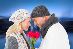 Composite image of smiling couple in winter fashion posing with roses Royalty Free Stock Photo