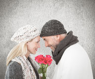 Composite image of smiling couple in winter fashion posing with roses Royalty Free Stock Photos