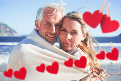 Composite image of smiling couple wrapped up in blanket on the beach Stock Image
