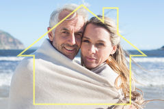 Composite image of smiling couple wrapped up in blanket on the beach Royalty Free Stock Photos