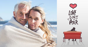 Composite image of smiling couple wrapped up in blanket on the beach Royalty Free Stock Images