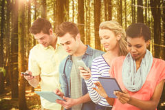 Composite image of smiling creative team standing in a line using technology. Smiling creative team standing in a line using technology against trees in a woods Royalty Free Stock Photography