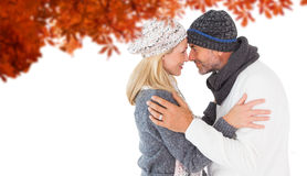 Composite image of smiling cute couple romancing over white background. Smiling cute couple romancing over white background against autumn leaves Stock Photo