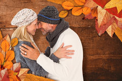 Composite image of smiling cute couple romancing over white background. Smiling cute couple romancing over white background against overhead of wooden planks Stock Images
