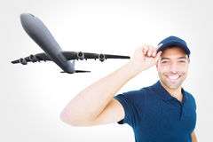 Composite image of smiling delivery man wearing cap on white background Royalty Free Stock Photo