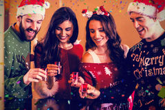 Composite image of smiling festive friends having shots Stock Photos