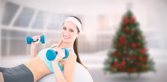 Composite image of smiling fit woman exercising with dumbbells on fitness ball. Smiling fit woman exercising with dumbbells on fitness ball against home with Stock Images