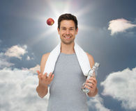 Composite image of smiling fit young man with apple and water bottle Stock Images