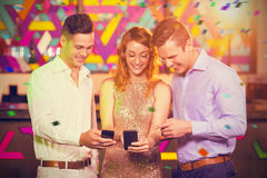 Composite image of smiling friend looking at mobile phone royalty free stock photography