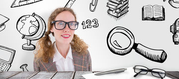 Composite image of smiling  geeky hipster girl looking at something. Smiling  geeky hipster girl looking at something against desk Royalty Free Stock Photos