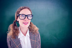 Composite image of smiling  geeky hipster girl looking at something. Smiling  geeky hipster girl looking at something against green chalkboard Royalty Free Stock Images